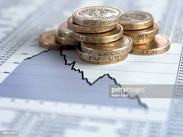 Stack of pound coins on descending line graph
