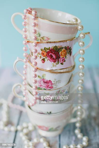 stack of pretty floral teacups draped with pearls - 服飾品 ストックフォトと画像