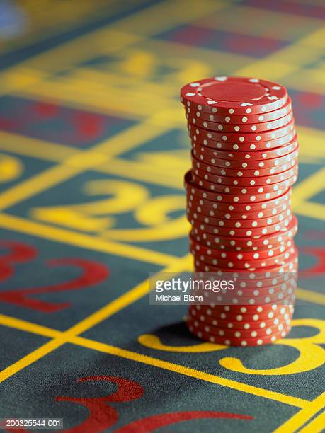 stack of red gambling chips on roulette table, close-up - roulette stock pictures, royalty-free photos & images
