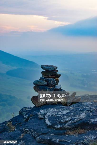 stack of rocks on shore against sky during sunset - stability stock pictures, royalty-free photos & images