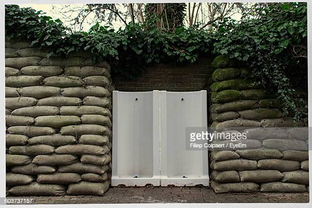 stack of sandbags against wall - sandbag stock pictures, royalty-free photos & images
