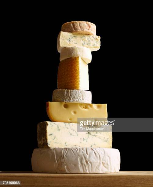 stack of selection of cheeses, against black background - cheese stock photos and pictures
