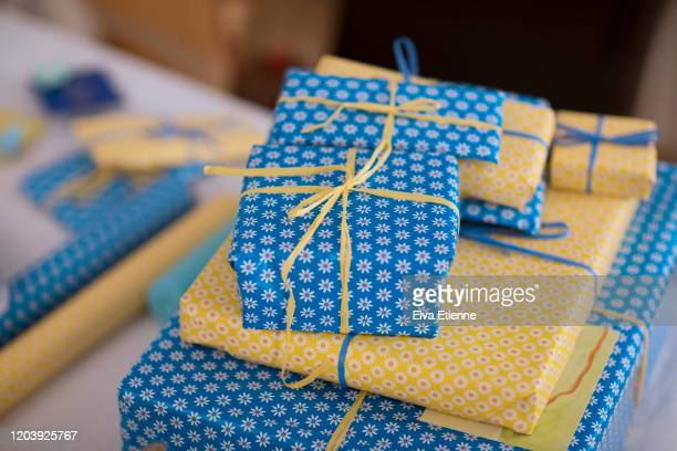 stack of several gifts wrapped in blue and yellow paper and tied with paper ribbon on a table - 誕生日の贈り物 ストックフォトと画像