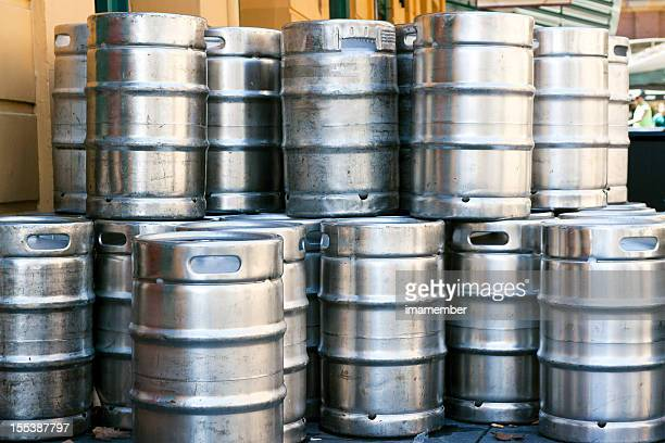 Stack of shiny stainless steel beer kegs outside of pub