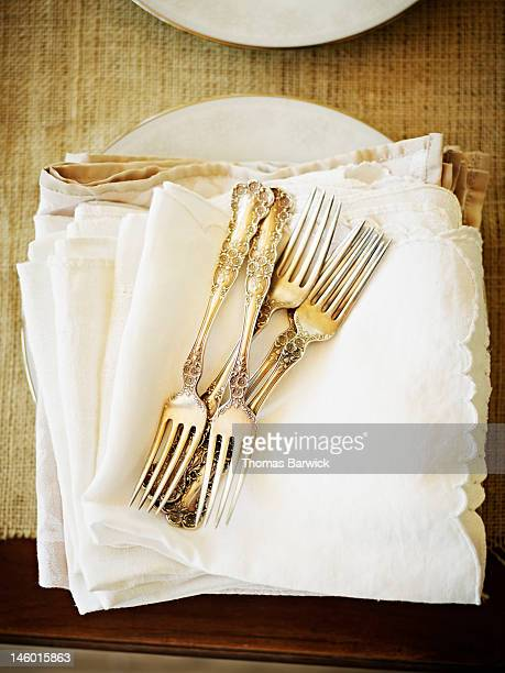 Stack of silver forks and napkins overhead view