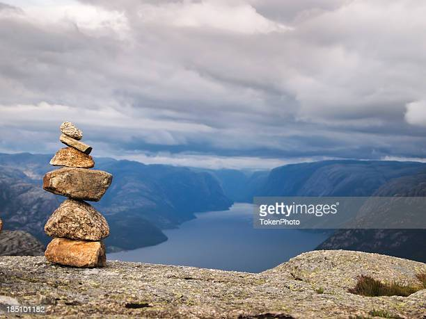 Stack of six rocks on top of a cliff with landscape view