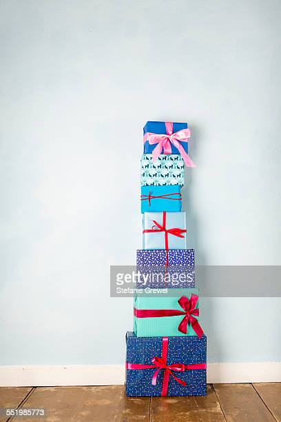 Stack of six wrapped christmas gifts on wooden floor
