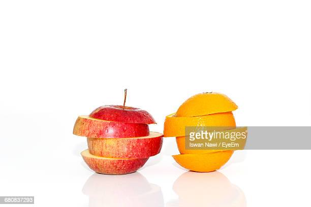 Stack Of Sliced Apple And Orange Against White Background