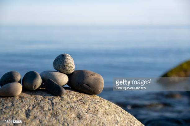 stack of small stones with the ocean in the background - finn bjurvoll stock pictures, royalty-free photos & images