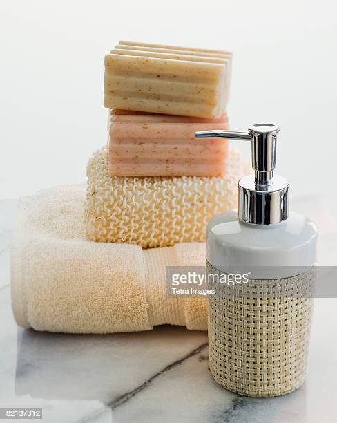 stack of soap and towels next to lotion - loofah stock photos and pictures