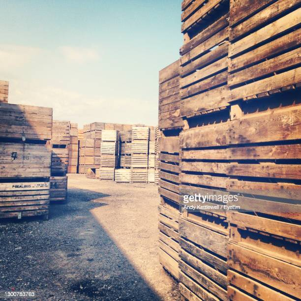 stack of stacks against sky in city - pallet industrial equipment stock pictures, royalty-free photos & images