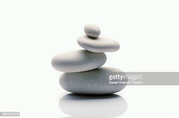 stack of stones against white background - pietra roccia foto e immagini stock