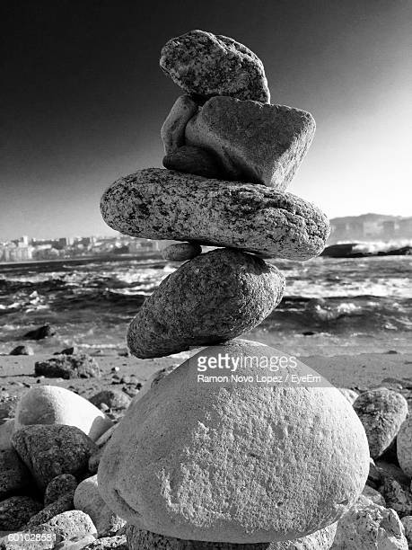 Stack Of Stones At Shore Against Sky