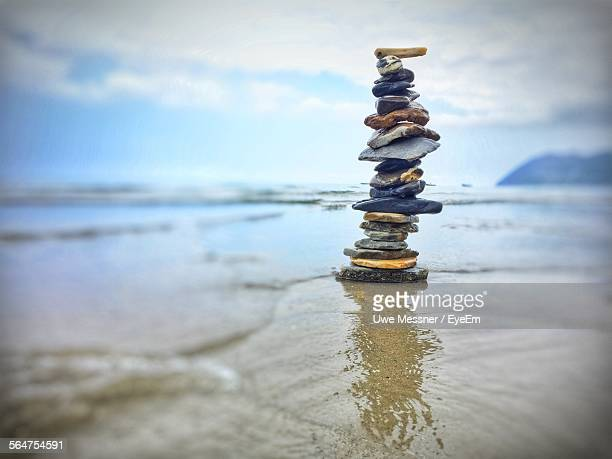 Stack Of Stones On Beach Against Cloudy Sky