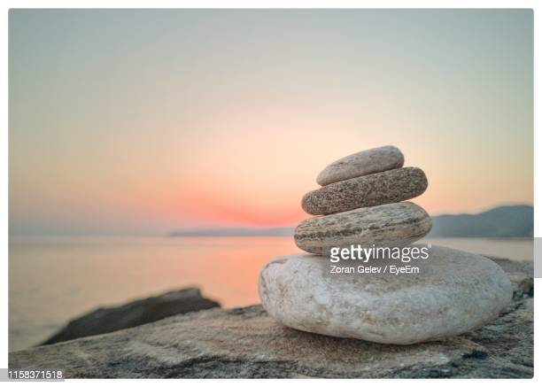stack of stones on beach against sky during sunset - transfer image stock pictures, royalty-free photos & images