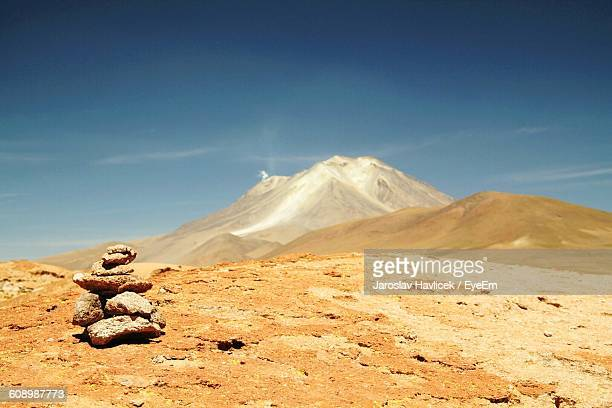 Stack Of Stones On Field By Mountains Against Sky