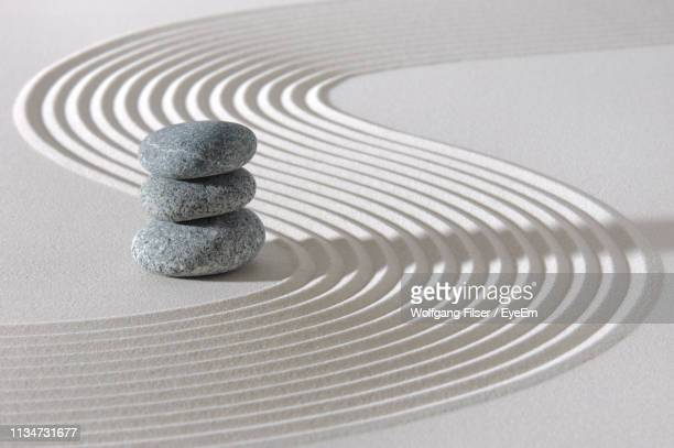 stack of stones on sand at beach - pebble stock pictures, royalty-free photos & images