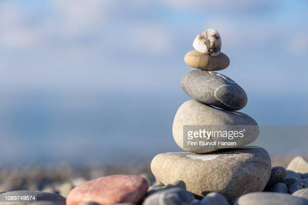 stack of stones on the beach with blurred background - finn bjurvoll stock photos and pictures