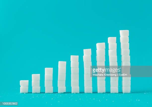 stack of sugar cubes against blue background - spoil system stock pictures, royalty-free photos & images
