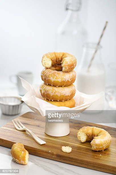 a stack of sugar glazed donuts on white background. - glazed food stock pictures, royalty-free photos & images