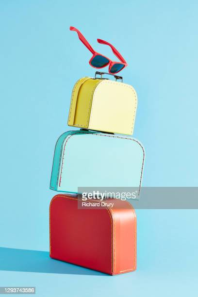 a stack of suitcases with a pair of sunglasses balanced on the top - holiday stock pictures, royalty-free photos & images