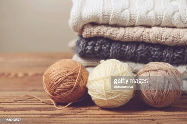 木製のテーブルにセーターのスタック - ウール ストックフォトと画像