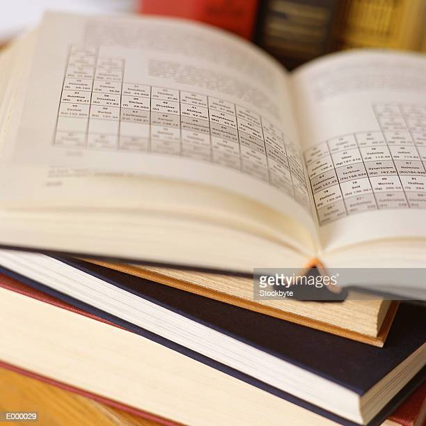 stack of textbooks; top book open, showing periodic table of elements - periodic table stock pictures, royalty-free photos & images