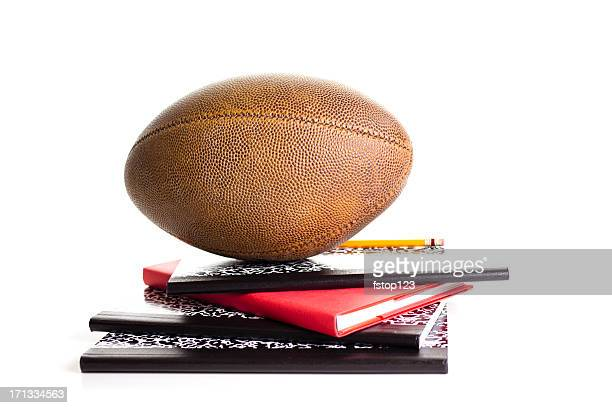 Stack of textbooks with football on top.  White background. Notebooks.