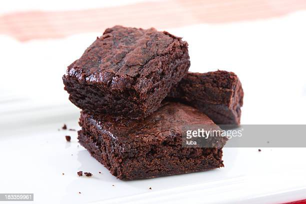 stack of three brownies on white plate - brownie stock pictures, royalty-free photos & images