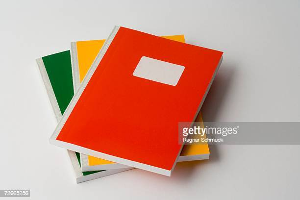stack of three colored workbooks - workbook stock photos and pictures