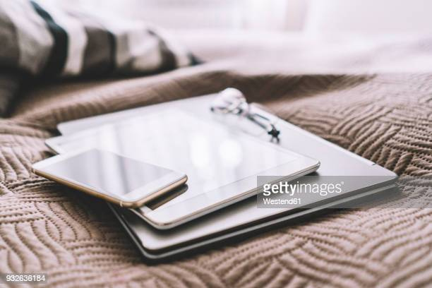 stack of three mobile devices on bed - differential focus stock-fotos und bilder