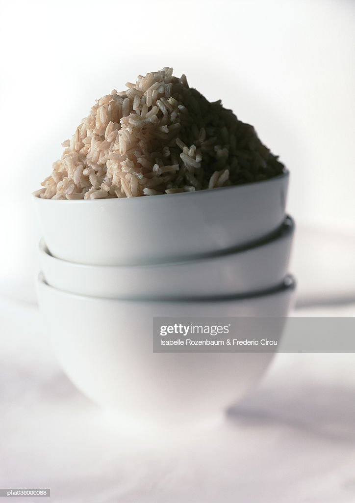 Stack of three white bowls, mound of brown rice in top bowl, close-up : Stockfoto