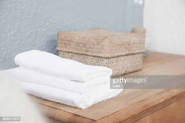 Stack of towels and box on dresser