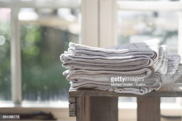 Stack Of Towels On Wooden Table Against Window At Home