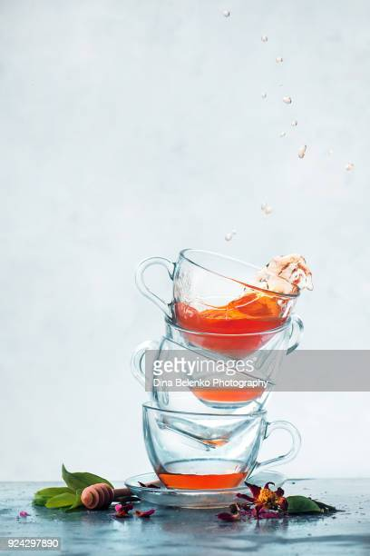 Stack of transparent tea cups balancing with a dynamic splash. Action still life photography with copy space, Frozen motion drink.