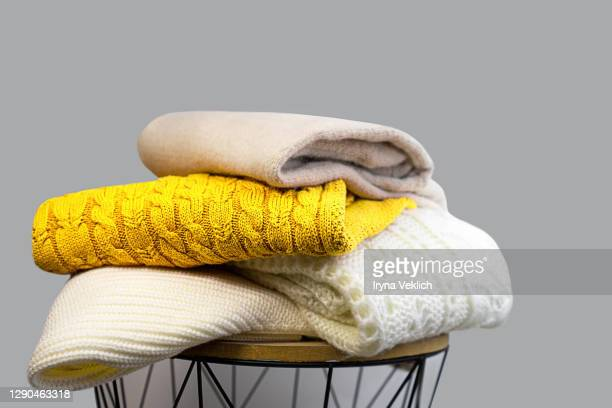 stack of trendy bright illuminating yellow, gray and white woolen knitted sweaters. - garment stock pictures, royalty-free photos & images