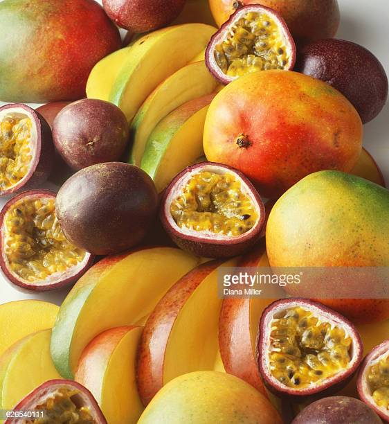 Stack of tropical fruit with mangoes and passion fruit, sliced and whole