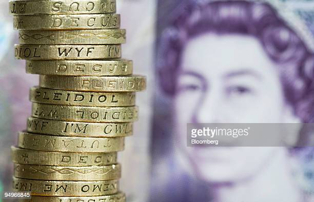 Stack of U.K. One pound coins sits next to a twenty pound note, arranged for a photograph in London, U.K., on Monday, Aug. 17, 2009. The pound's...