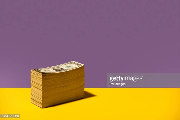 Stack of US $1 bills sitting on yellow background