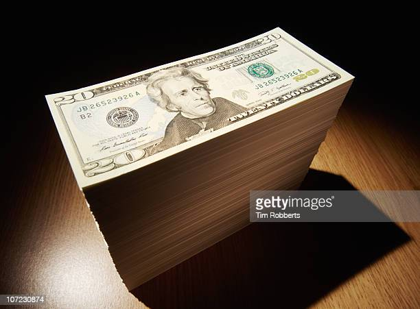 Stack of US$20 notes in spotlight