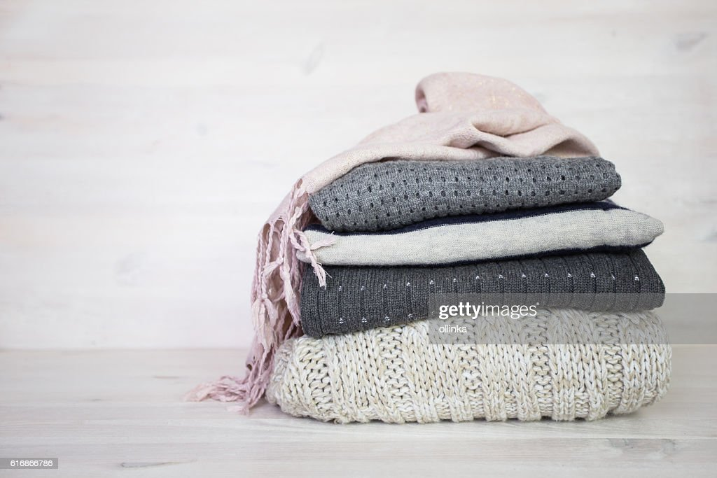 stack of various woolen sweaters on a white wooden background : Stock Photo