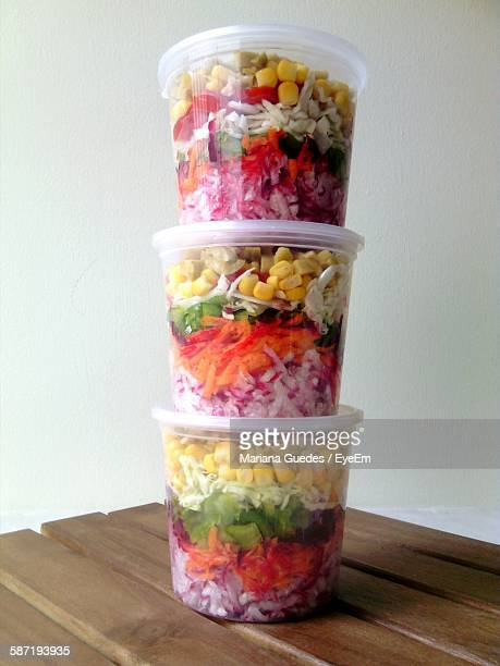 Stack Of Vegetable Salad In Container On Table Against Wall At Home