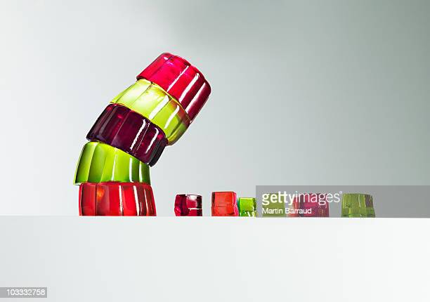 stack of vibrant gelatin dessert leaning over small gelatin dessert cubes - tower stock pictures, royalty-free photos & images
