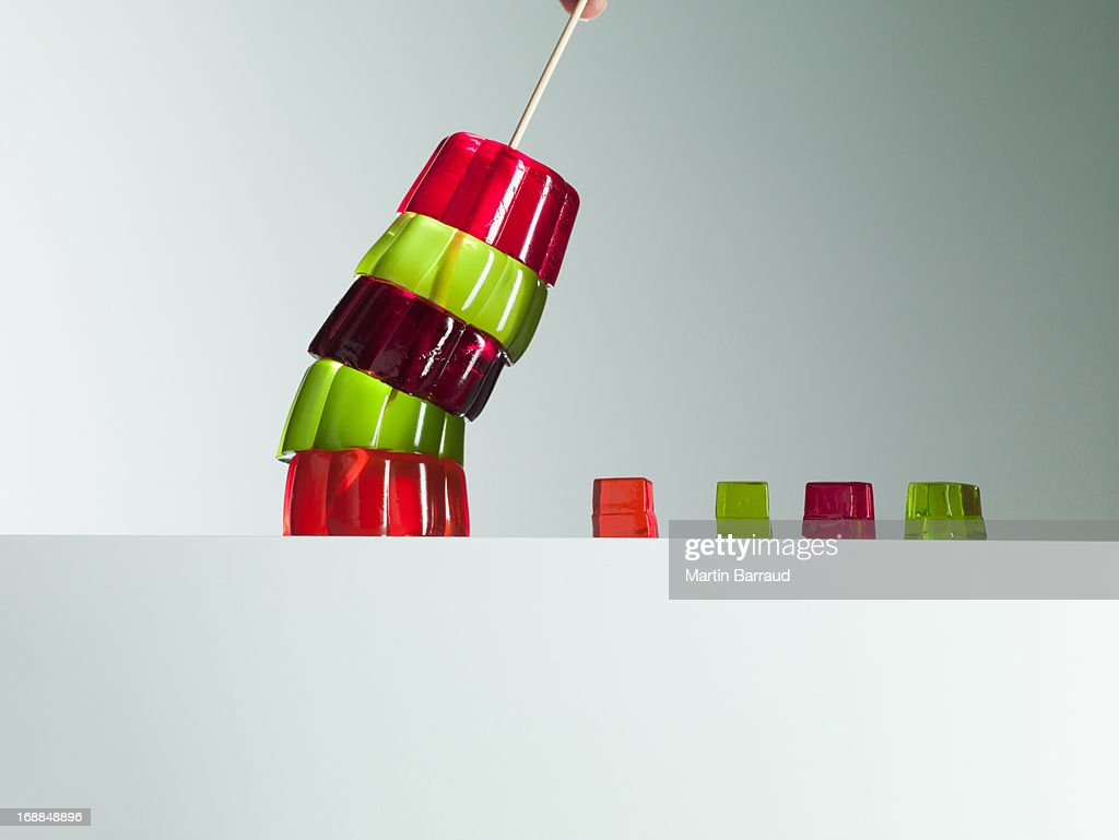 Stack of vibrant gelatin dessert leaning over small gelatin dessert cubes : Stock Photo