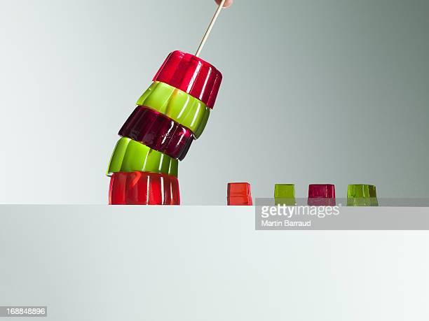 Stack of vibrant gelatin dessert leaning over small gelatin dessert cubes