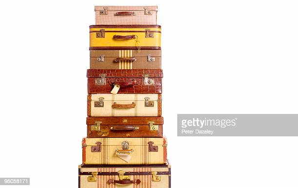 stack of vintage suitcases against white