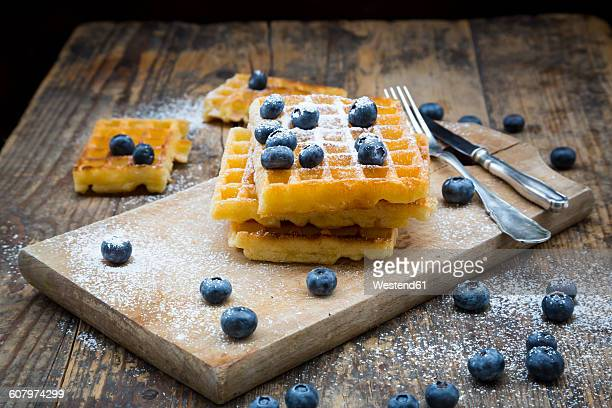 Stack of waffles with icing sugar and blueberries