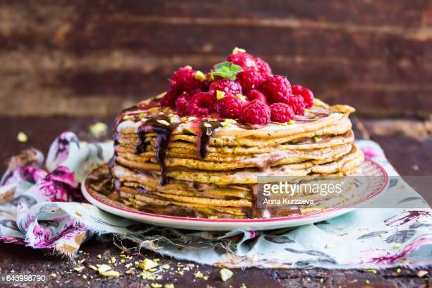 stack of wheat golden pancakes or pancake cake with freshly picked raspberry, chopped pistachios, chocolate sauce on a dessert plate, selective focus - crepes photos et images de collection