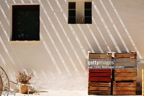 Stack Of Wooden Crates Against House Wall