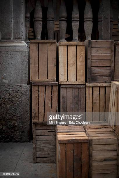 a stack of wooden crates, in the corner of a room.  - crate stock pictures, royalty-free photos & images